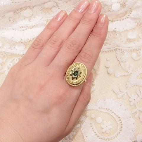 エメラルドとエナメルの指輪をつけた写真です。