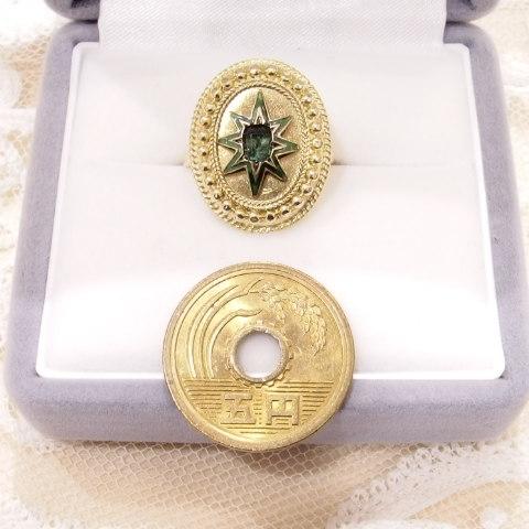 エメラルドとエナメルの指輪の隣に5円玉を置いています。